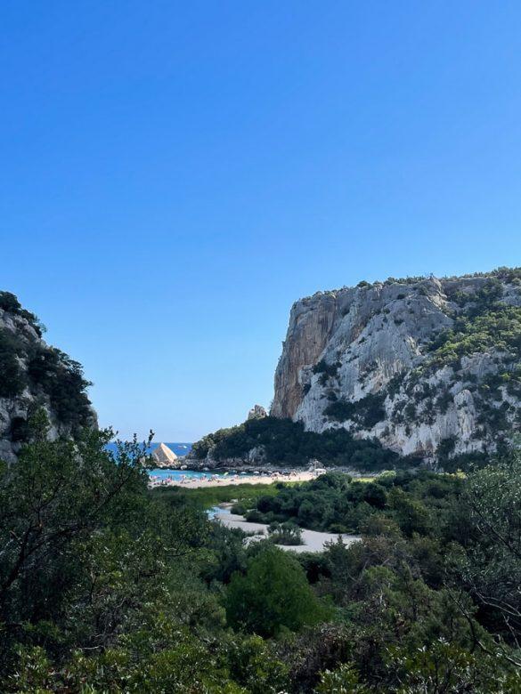 pogled na plažo Cala Luna s peš poti: bela plaža v zalivu, ob strani sive pečine in gostjo zelenje