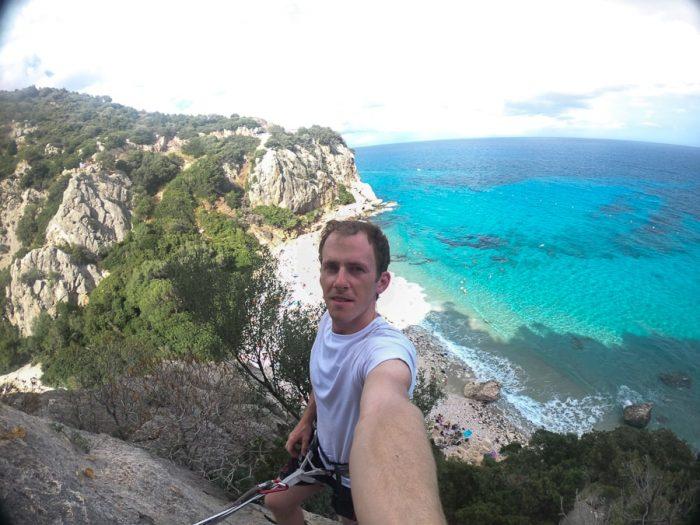 moški na vrhu plezališča nad plaži Cala Fuili