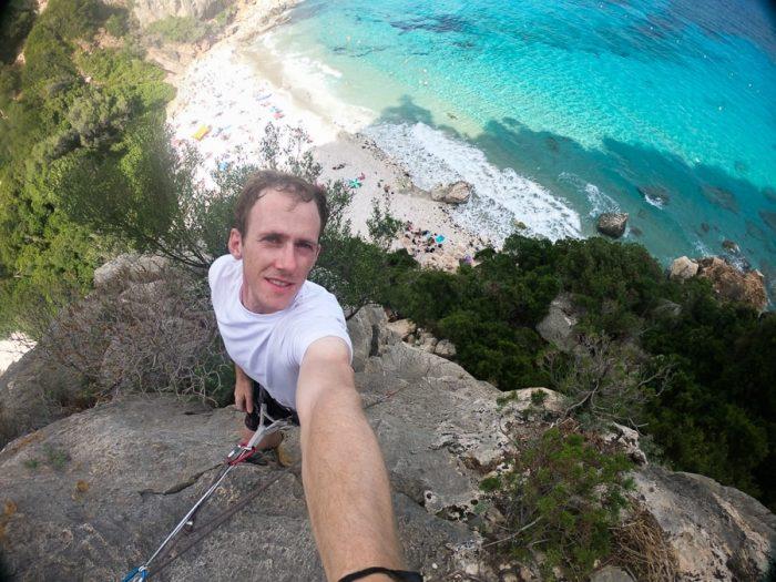 moški na vrhu plezalne smeri nad plažo Cala fuili