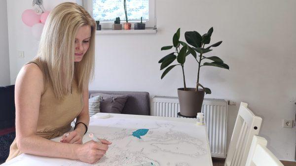 ženska riše zemljevid sveta za barvanje