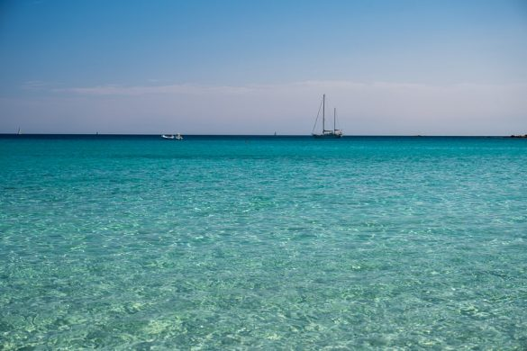 Top znamenitosti Sardinije: plaže! turkizno modro morje in jadrnica v daljavi