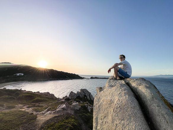 moški sedi na skali nad plažo Rena Bianca in opazuje sončni zahod